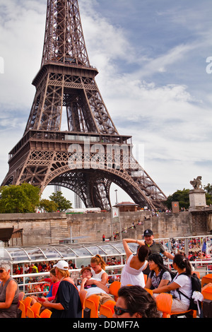 Tourists photographing the Eiffel Tower from the Bateaux Mouches in Paris. - Stock Photo