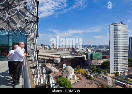 Birmingham, UK. 4th September 2013. View of the Birmingham skyline with people on the upper roof garden of the Library - Stock Photo