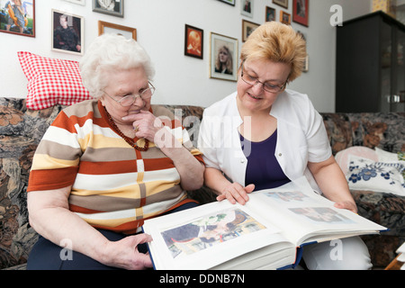 Geriatricnurse and old woman looking into photo album - Stock Photo