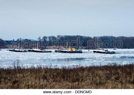 Four icebreakers on River Elbe at Zollenspieker, Hamburg, Germany - Stock Photo