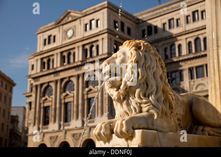 marble lion of the fountain Fuente de los Leones and Havana Stock Exchange / Lonja del Comercio building on Plaza - Stock Photo