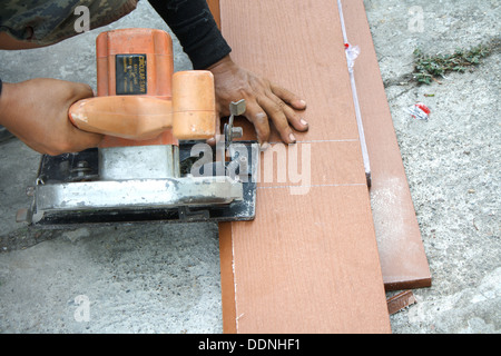 Workers are using a circular saw to cut wood. - Stock Photo