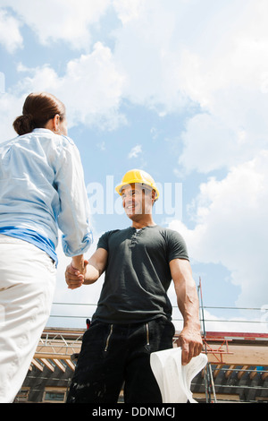 Foreman and client shaking hands on construction site - Stock Photo