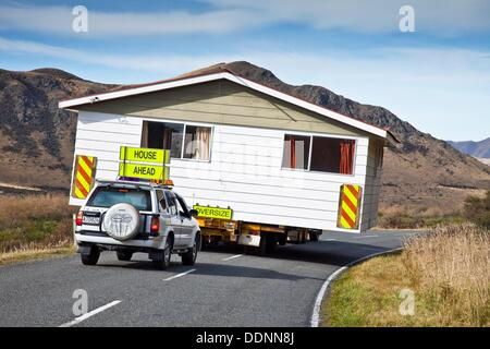 House being relocated by truck and escort vehicles, Mt. Somers, Canterbury, New Zealand - Stock Photo