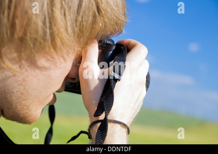 Young Photographer taking a photograph using a DSLR camera outdoors - Stock Photo