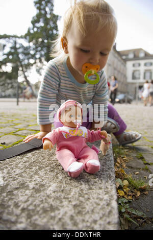 Baby girl playing with doll in the streets of Zürich, Switzerland. - Stock Photo