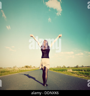 Happy woman standing with hands up on straight road facing sun. Future / freedom / hope / success concept - Stock Photo