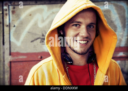 Teen / Young man portrait in hooded sweatshirt / jumper on grunge graffiti wall - Stock Photo