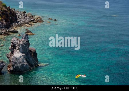 People on rafts in a rocky bay near Malfa on the island of Salina, The Aeolian Islands, Messina, Sicily, Italy - Stock Photo