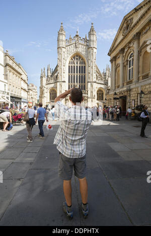A man is photographed taking a photo of Bath Abbey,BathSomerset,UK - Stock Photo