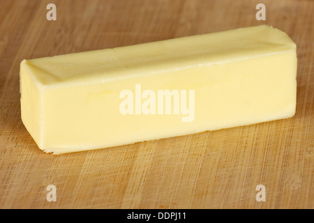 Stick of table butter on a cutting board - Stock Photo