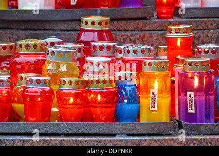 Lot of illuminated votive candles glows on a grave - Stock Photo