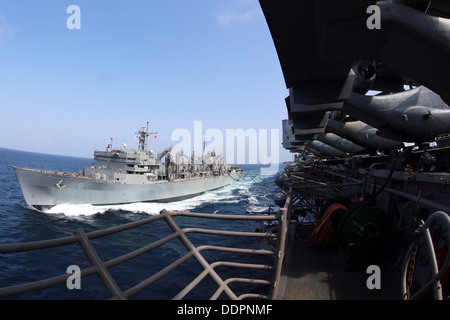 The amphibious assault ship USS Kearsarge (LHD 3) conducts a replenishment-at-sea with the fast combat support ship - Stock Photo