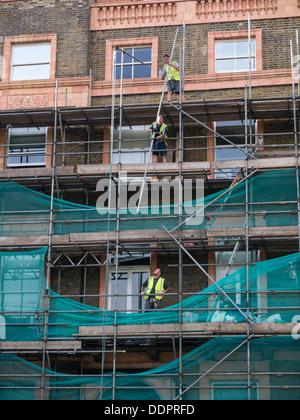 Workmen deconstructing scaffolding in Bloomsbury, London - Stock Photo