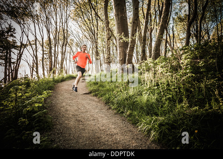 A yong man running on a trail through the forest in Discovery Park, Seattle, Washington, USA. - Stock Photo