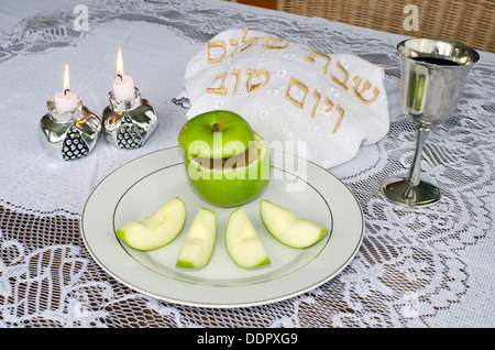 Jewish New Year - Rosh Hashanah , apple with honey, candles ,challah and wine cup on the Seder table. - Stock Photo