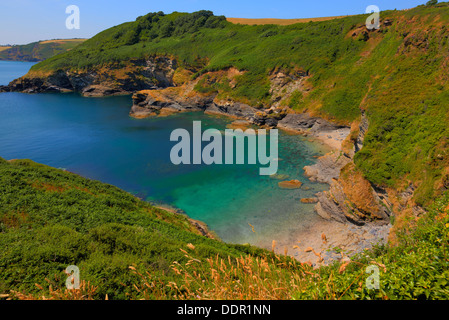 Secluded beach and cove with turquoise sea Black Head headland St Austell Bay between Porthpean and Pentewan Cornwall - Stock Photo