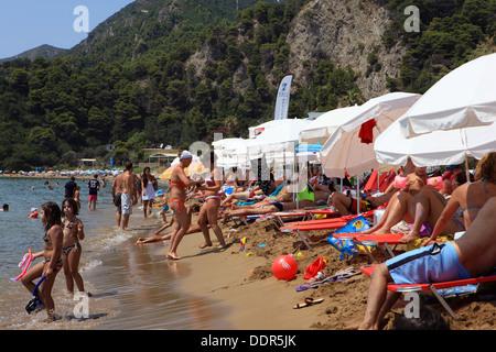 Busy Glyfada beach on the Corfu island in Greece - Stock Photo
