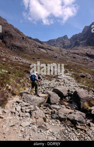 Female hillwalker on footpath to Coire Lagan and Sgurr Alasdair in the Black Cuillin Mountains, Isle of Skye, Scotland, - Stock Photo