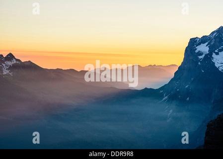 Dawn from the summit of the Rotstock above Grindelwald Switzerland with the Wetterhorn on the right - Stock Photo