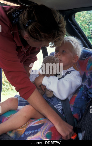 mother strapping little boy into car seat - Stock Photo