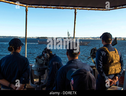 Sailors observe the Japan Maritime Self-Defense Force destroyer Takanami (DD 110) from the bridge wing of the guided - Stock Photo
