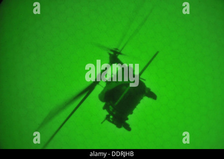 A U.S. Air Force HH-60G Pave Hawk helicopter from the 101st Rescue Squadron conducts a nighttime live fire exercise - Stock Photo