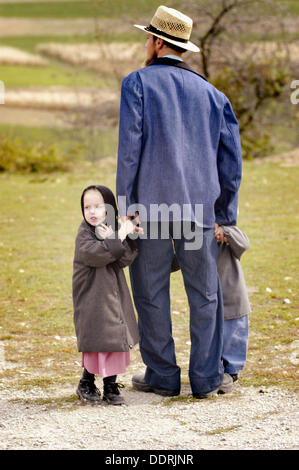 Amish of the American Heartland:  Ohio, Indiana, Pennsylvania. Family at market, dad and children holding hands. - Stock Photo