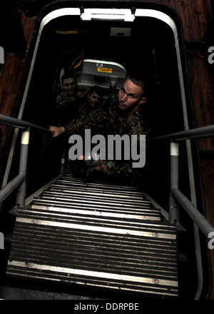 Seabees from Naval Mobile Construction Battalion (NMCB) 3 climb a ladderwell while touring USS Stethem (DDG 63). - Stock Photo