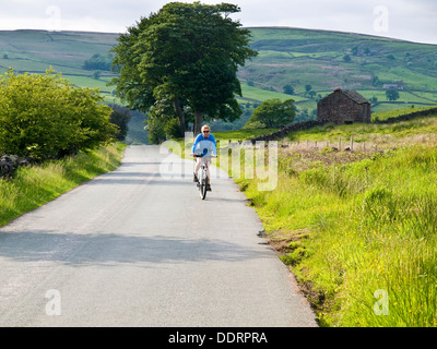 Female cycling near Gradbach in the Staffordshire Moorlands, Peak District National Park - Stock Photo