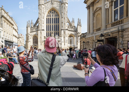 Tourists are shown photographing Bath Abbey and the pump rooms in Bath,Somerset,England,UK. - Stock Photo