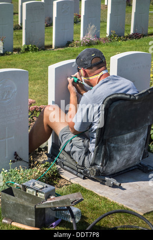 Engraver restoring headstone at Tyne Cot Cemetery of the Commonwealth War Graves Commission for World War One British - Stock Photo