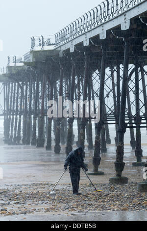 Man metal detecting in the rain with metal detector on beach. UK - Stock Photo