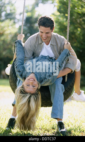 couple on a tire swing - Stock Photo