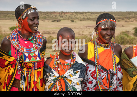Masai women wearing colorful traditional dress, singing in a village near the Masai Mara, Kenya, Africa - Stock Photo