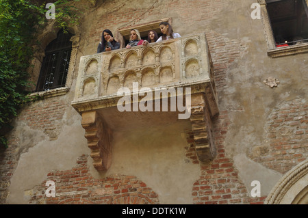 Four young would-be Juliets look out from her balcony in the Casa Di Giulietta, Verona. - Stock Photo
