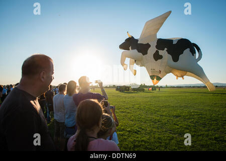 Piestany, Slovakia. 6th September 2013. Crowds watch as Swiss crew blast the flame into cow shape balloon during 1st Balloon megafiesta on September 6th, 2013 in Piestany, Slovakia Credit:  Lubos Paukeje/Alamy Live News
