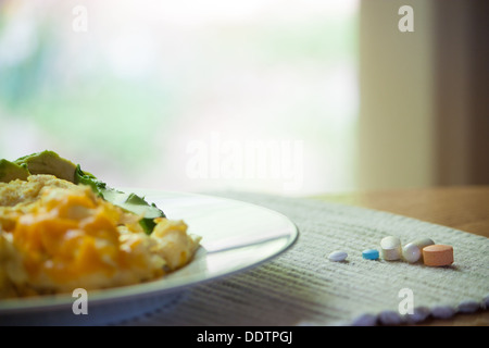 an aray of vitamins beside a breakfast of scrambled eggs florentine with cheese. Focus is on vitamins. Window light - Stock Photo