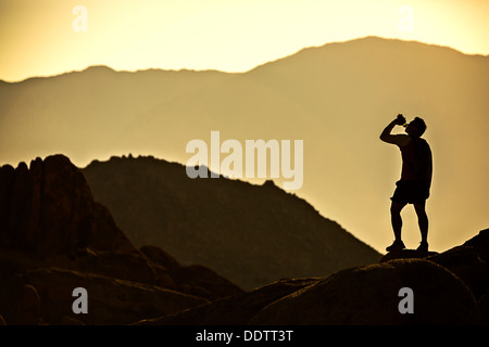 A lone runner in the mountains stops for a drink from his water bottle and is silhouetted by the morning sun. - Stock Photo