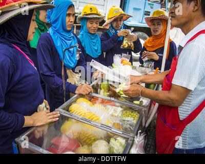 Aug. 18, 2013 - Bangkok, Thailand - Migrant construction workers from Myanmar (Burma) buy fruit from a Thai fruit - Stock Photo