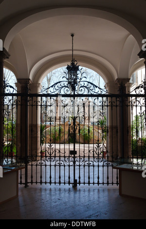 Palazzo courtyard with arched ceiling, wrought iron hanging  lamp, gate leading to open area with wrought iron fencing, - Stock Photo