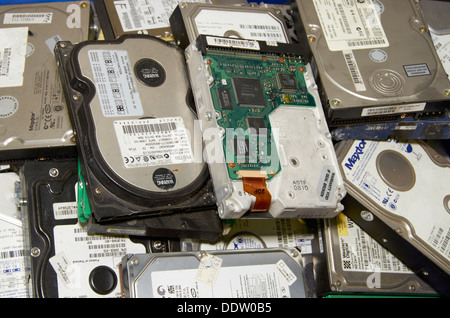 Computer hard drives waiting to be stripped down (recycled) for their precious metals and valuable magnets. - Stock Photo