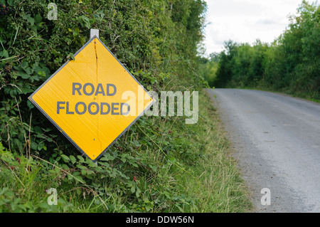Yellow road sign on a rural road warning that the road is flooded - Stock Photo