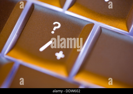 Close up of the question mark on an illuminated computer keyboard - Stock Photo