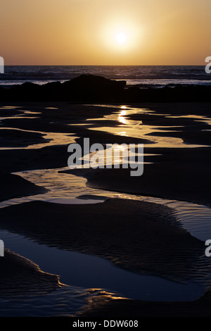 Bright orange setting sun reflects in the meandering rivulets of water on Porthtowan Beach in Cornwall, UK - Stock Photo