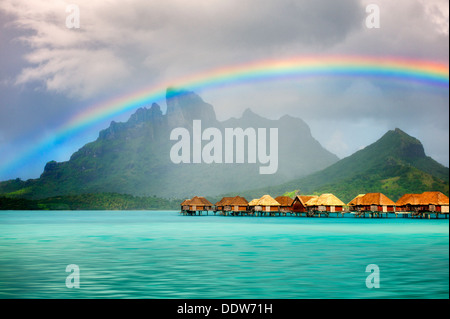 Bungalows over water with rainbow and Mt. Otemanu. Bora Bora. French Polynesia - Stock Photo