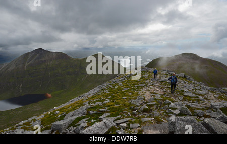 Two male walkers on western ridge of Sail Gharbh (a Corbett) on the Scottish mountain Quinag heading towards Spidean - Stock Photo