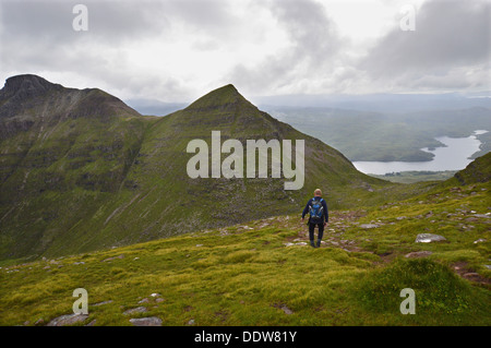Lone male walker on western ridge of Sail Gharbh (a Corbett) on the Scottish mountain Quinag heading towards Spidean - Stock Photo