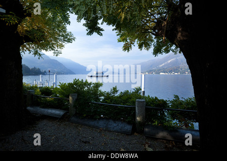View of Bellagio lakefront in early morning sunshine, autumn colours of beech trees, passenger ferry leaving dock, - Stock Photo