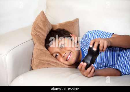Young boy playing computer game while relxing on the sofa - Stock Photo